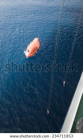 Lowered orange lifeboat in offshore, rescue boat or rescue team in the sea. - stock photo