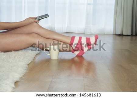 Lowsection of a woman in stripey socks holding remote control - stock photo