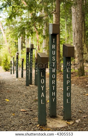 Loyal, trustworthy and helpful are three adjectives that describe boy scouts. These signs line a dirt path to a campfire ground at a boy scout camp. - stock photo