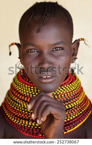 LOYANGALANI - KENYA - JANUARY 22, 2015: Unidentified beautiful Turkana woman with traditional headdress and necklace on January 22, 2015 in Loyangalani, Kenya.  - stock photo