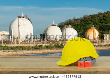 LPG gas storage sphere tanks and yellow Safety Helmet with blue sky background in Thailand - stock photo