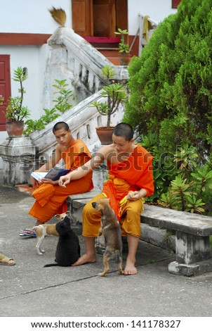 LUANG PRABANG, LAOS - SEPTEMBER 5: Unidentified monks in Wat Mai temple on September 5, 2011, in Luang Prabang, Laos. about 60% of the population of Laos practice Theravada Buddhism. - stock photo