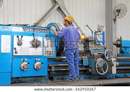LUANNAN COUNTY - AUGUST 25: Industrial workers on machine in a production line, Xinxin special steel co., LTD, On August 25, 2011, luannan county, hebei province, china. - stock photo