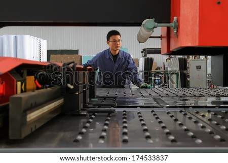 LUANNAN COUNTY, CHINA - NOV 24, 2012: A worker was operating CNC machine tools, in the DingRe Solar Energy Ltd, in November 24, 2012, Luannan County, china.   - stock photo