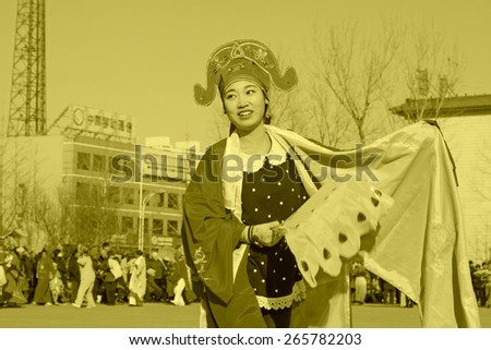 LUANNAN COUNTY - FEBRUARY 9: Girl wearing colorful clothes, performing yangko dance in the street, during the Chinese Lunar New Year, February 9, 2014, Luannan County, Hebei Province, China.  - stock photo