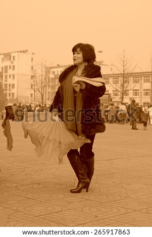 LUANNAN COUNTY - FEBRUARY 15: Woman wearing colorful clothes, performing yangko dance in the street, during the Chinese Lunar New Year, February 15, 2014, Luannan County, Hebei Province, China. - stock photo