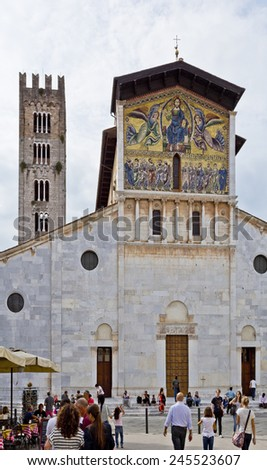 LUCCA, ITALY - SEPTEMBER 3, 2014: The Romanesque Basilica of San Frediano in Lucca, Tuscany, Italy, with the monumental golden mosaic on the facade - stock photo