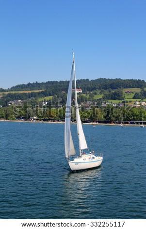 LUCERNE,SWITZERLAND, JUNE 28,2015: White sailboat sailing lake Lucerne in Switzerland under sunny skies - stock photo