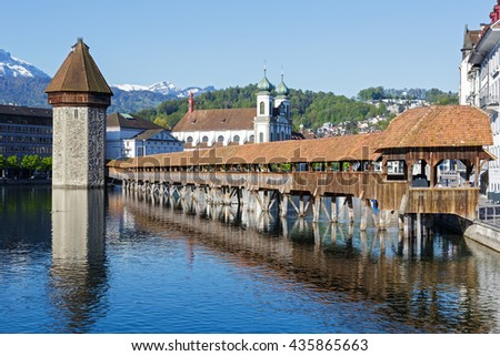 LUCERNE, SWITZERLAND - MAY 05, 2016: View towards Chapel Bridge together with the octagonal tall tower, it is one of the Lucerne's most famous tourists attraction  - stock photo