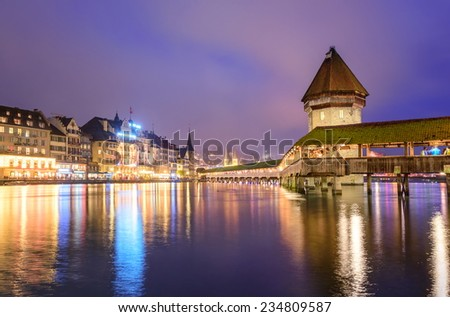 Lucerne, Switzerland, night view over the Reuss river to the wooden Chapel bridge and Water Tower - stock photo