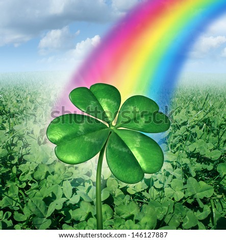Luck concept with a four leaf clover over a field of green clovers with a rainbow from the sky shinning down as a symbol of good fortune and prosperity as a metaphor for success and opportunity. - stock photo