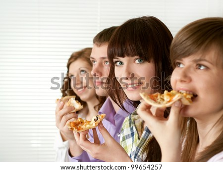 Luck funny Caucasian campaign of four people eating pizza on a light background - stock photo