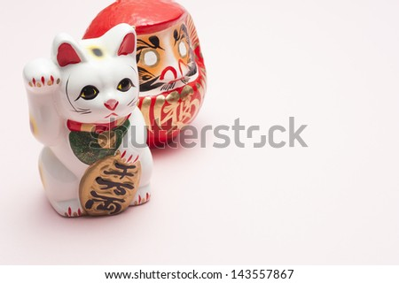 lucky cat and dharma on pink background - stock photo