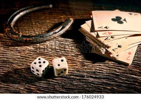 Lucky craps game dice rolling out chance number seven and vintage poker cards with winning aces by old horseshoe for player and gambler good luck charm on rustic wood table in western gambling saloon - stock photo