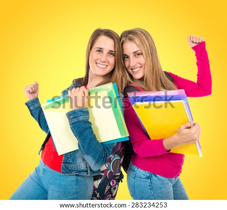 Lucky students over colorful background - stock photo