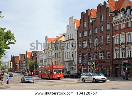 LUEBECK, GERMANY - MAY 26, 2011: Street with a tourist bus is shown on May 26, 2011 in Luebeck, Germany. Many tourists visit Luebeck because the city is in UNESCO List of Heritage. - stock photo