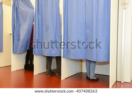 Lugano, Switzerland - 11 april 2016: row of tree voting booths with men and women casting their ballots at the municipal election of Lugano on Switzerland - stock photo