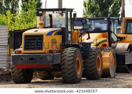 LUGANSK, UKRAINE - JULY 30, 2008: yellow industrial trucks on construction of road, Lugansk, Ukraine. - stock photo