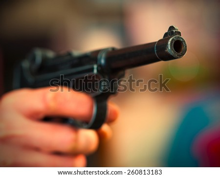 Luger Parabellum automatic pistol in a human hand, shallow depth of field. close-up. instagram image retro style - stock photo