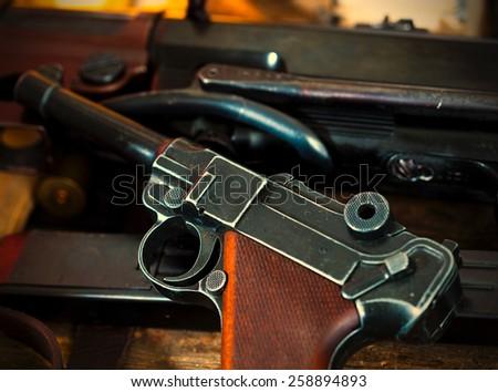 Luger Parabellum pistol and submachine gun MP 38 in gunsmith. instagram image retro style - stock photo