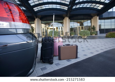 Luggage beside parked car outside hotel - stock photo