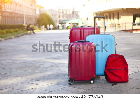 Luggage consisting of three large suitcases and travel backpack on the street. Holiday and travel concept - stock photo