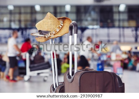 Luggage with straw hat at the airport terminal - stock photo