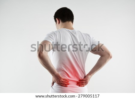 Lumbago symptom. Young man holding his painful inflamed loin. Health care and medicine.  - stock photo