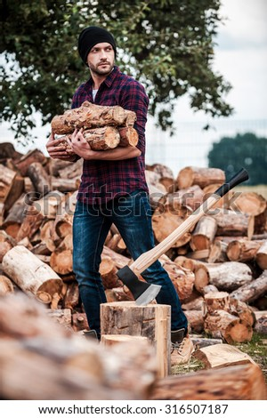 Lumberjack at work. Handsome young forester holding logs and looking away while standing outdoors - stock photo
