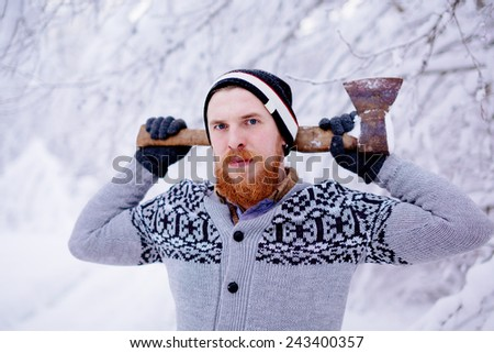 Lumberjack in the snowy winter forest. A man with a red beard and ax posing in a snowy winter forest. - stock photo