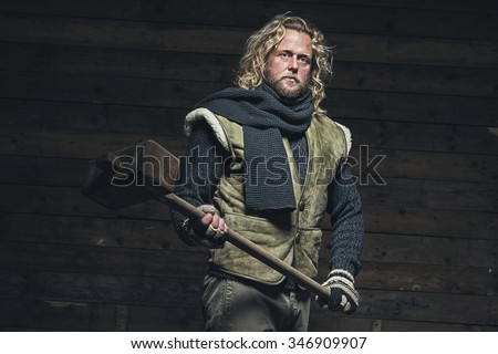 Lumberjack Winter Fashion Man Long Blonde Hair and Beard. Holding Wooden Hammer. Standing in Barn. - stock photo