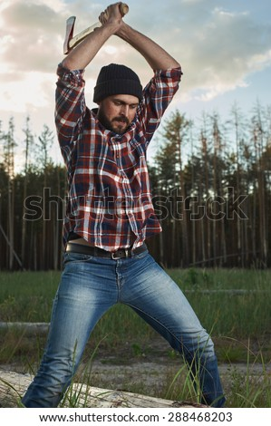 Lumberjack with Beard, Hat and Shirt swings the Ax on a Tree - stock photo