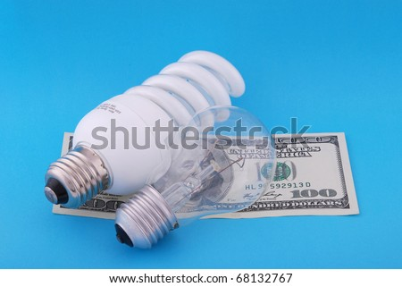 Luminescent and electric lamp on hundred dollars. On blue background - stock photo