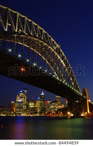 Luminous Sydney Harbor Bridge at night with colorful lighting and the skyline of the city center in vertical frame - stock photo