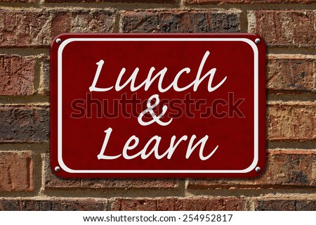 Lunch and Learn Sign,  A red sign with the word Lunch and Learn on a brick wall - stock photo