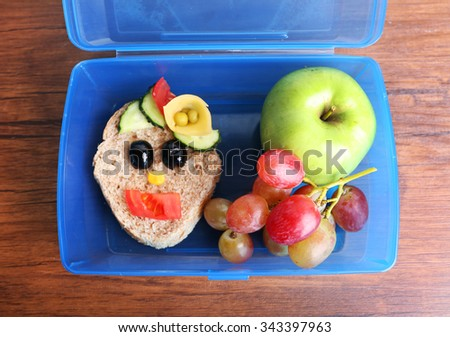 Lunch box with creative sandwich and fruits on wooden background - stock photo