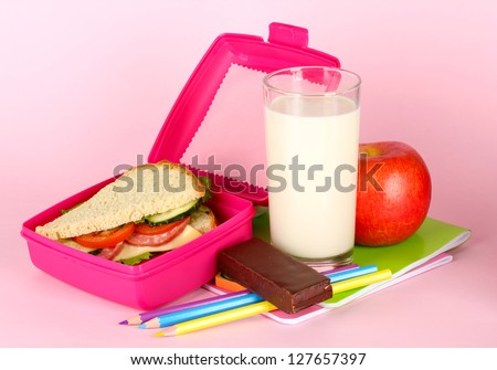 Lunch box with sandwich,apple,milk and stationery on pink background - stock photo