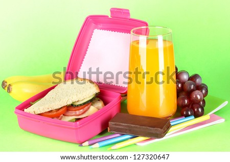 Lunch box with sandwich,fruit,juice and stationery on green background - stock photo