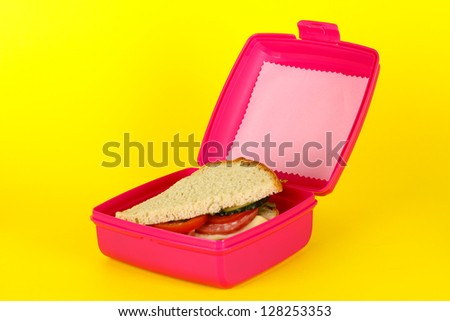 Lunch box with sandwich on yellow background - stock photo