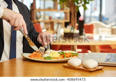 Lunch break. Cropped closeup of a businessman cutting food on his plate during business lunch in the restaurant - stock photo
