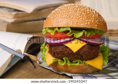 Lunch during study: Fresh big hamburger on a background of notebooks and textbooks. closeup horizontal - stock photo