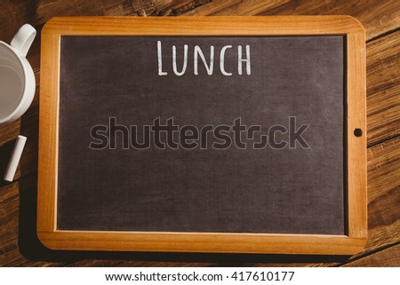 Lunch message against chalkboard on desk - stock photo