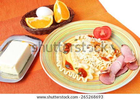 Lunch served on a bright color napkin - Pasta with tomato sauce, grated parmesan cheese,rolls of beef pastrami, grains of pumpkin, herbs and fresh tomato with addition of butter,eggs and sliced orange - stock photo