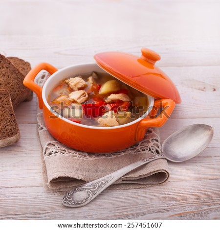 Lunch time. Fresh chicken soup with vegetables on white wooden table. Cutlery on linen tablecloth. rustic style - stock photo