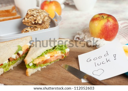 Lunchbox on breakfast table with a good luck message - stock photo