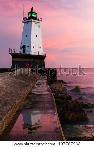 Lundington (Michigan) North Breakwater Light with reflection and Sundown Sky - stock photo