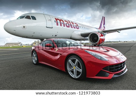 LUQA, MALTA - DEC 09 - Ferrari F12 supercar next to an AirMalta Airbus A320, after their race challenge on Sunday 9 December 2012 - stock photo