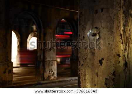 Lurking in the Shadows - Phantom of the Opera Mask in Dark Tunnel - stock photo