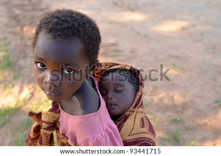 LUSAKA,ZAMBIA–DECEMBER 3:unidentified child with her brother .Many children are out of school to care for siblings when parents work in the fields,on December 3,2011 in Lusaka,Zambia - stock photo