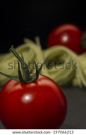 Luscious ripe red fresh tomato with an attached green stalk with Italian pasta ready to cook a traditional Mediterranean meal, vertical format on a dark background with copyspace - stock photo